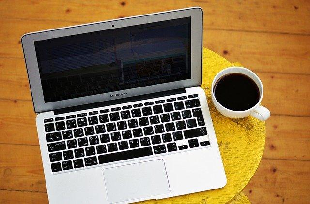 laptop a káva na žluté stoličce