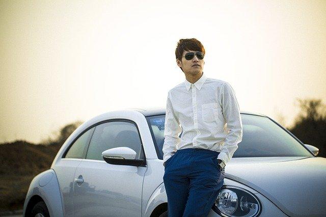 muž opřený o automobil