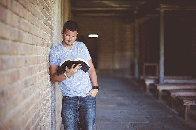muž s knihou u zdi