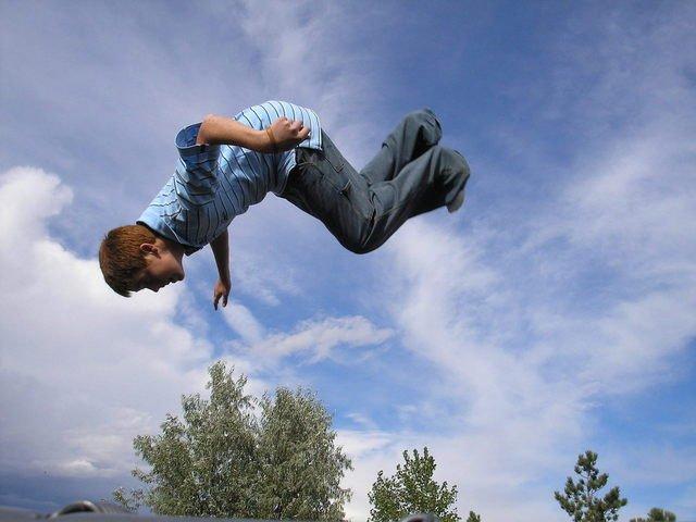 dítě skákající na zahradní trampolíně