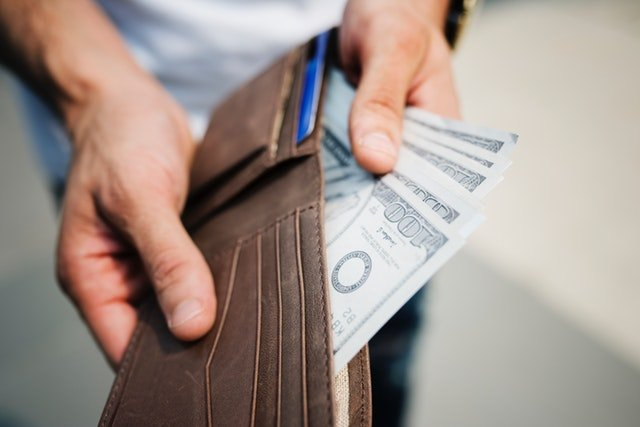 ruce vytahují sto dolarovky z peněženky
