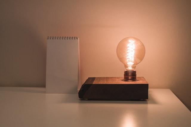 žárovka na knize vedle bločku
