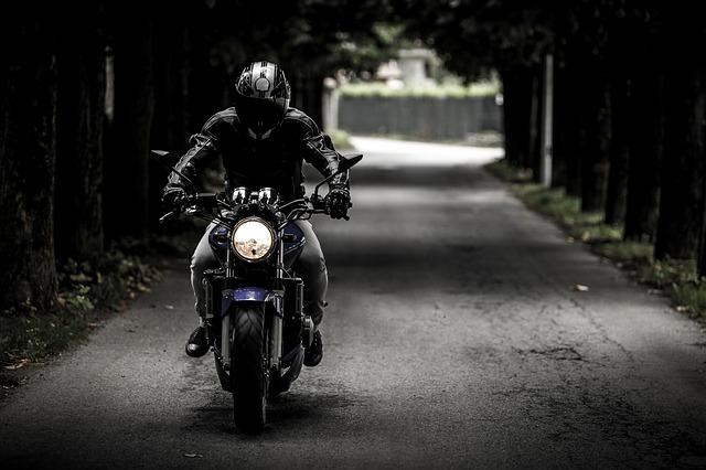 motorkář na cestě uprostřed lesa